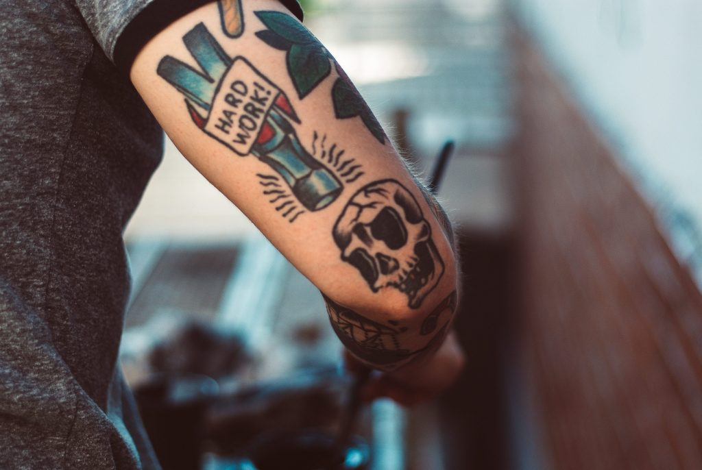 Colorful tattoo that says hard work and a skull